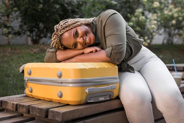 Szczęśliwa kobieta przebywa na jej bagażu z głową