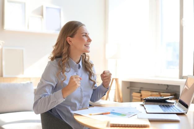 Szczęśliwa kobieta przedsiębiorca siedzieć przy biurku, czytając dobre wieści i wyrażać radość rosnące ręce do góry.