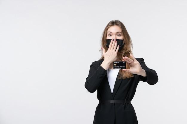 Szczęśliwa kobieta przedsiębiorca w garniturze, ubrana w maskę medyczną i pokazująca kartę bankową, wykonującą gest ciszy na białym tle