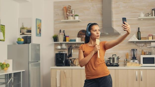 Szczęśliwa kobieta przy selfie rano podczas śpiewania za pomocą łyżki. energiczna, pozytywna, szczęśliwa, zabawna i urocza gospodyni tańcząca samotnie w domu. rozrywka i wypoczynek samemu w domu