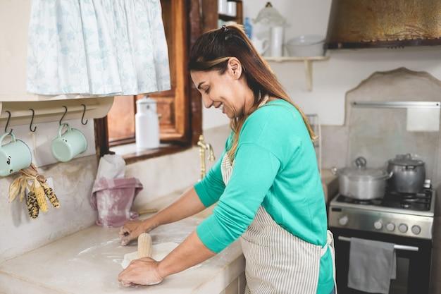 Szczęśliwa kobieta przygotowuje fajitas wrap w domu wewnątrz kuchni vintage - koncepcja domowej roboty żywności - skupić się na uchu