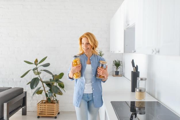 Szczęśliwa kobieta przygotowuje się do ugotowania świeżego śniadania w kuchni.