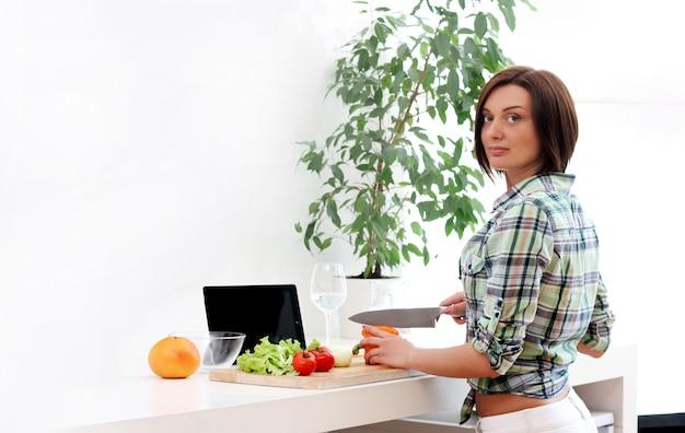 Szczęśliwa kobieta przygotowywa zdrowej sałatki