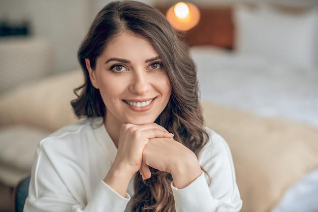 Szczęśliwa kobieta. przystojna młoda kobieta w białej bluzce ładnie się uśmiecha i wygląda na szczęśliwą
