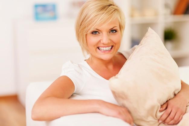 Szczęśliwa kobieta przytulanie poduszkę i odpoczynek w domu