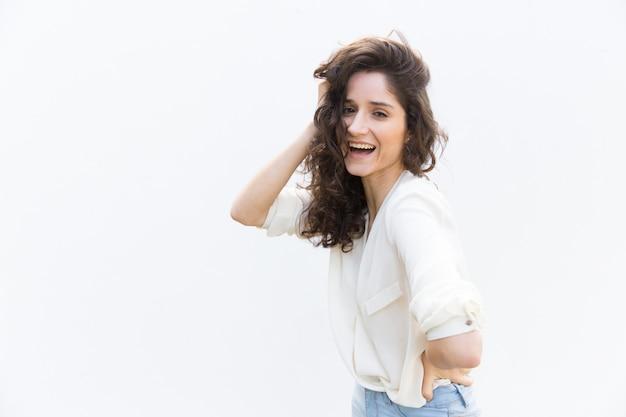 Szczęśliwa kobieta radosna, dotykając kręcone włosy i śmiejąc się