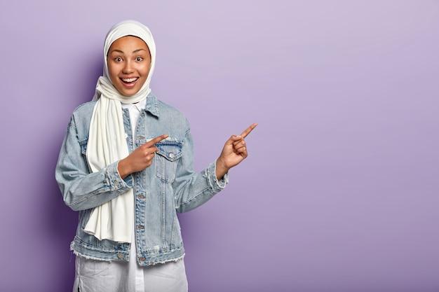 Szczęśliwa kobieta rasy mieszanej ma wesoły wyraz twarzy, wskazuje obiema palcami przednimi, mówi podążaj za nimi, wskazuje kierunek nad przestrzenią kopii, nosi dżinsowe ubrania, biały hidżab, odizolowany na fioletowej ścianie