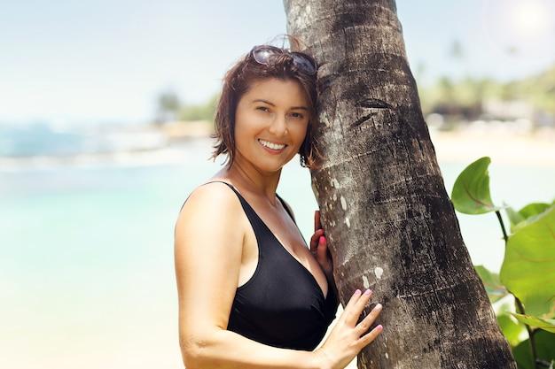 Szczęśliwa kobieta relaksuje się na plaży latem