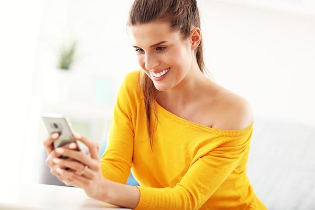 Szczęśliwa kobieta relaksuje się w domu ze smartfonem