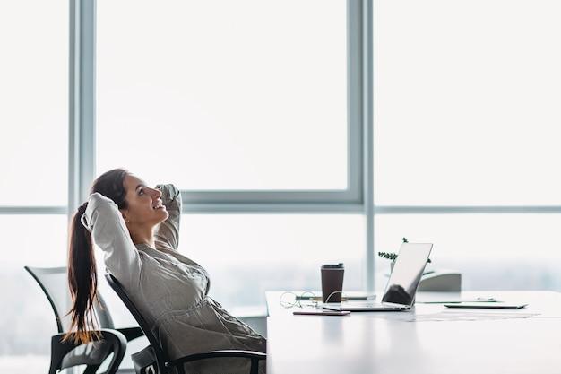 Szczęśliwa kobieta relaksuje się z rękami za głową przy biurku marzy koncepcja widok z boku