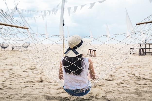 Szczęśliwa kobieta relaksuje w hamaku na plaży