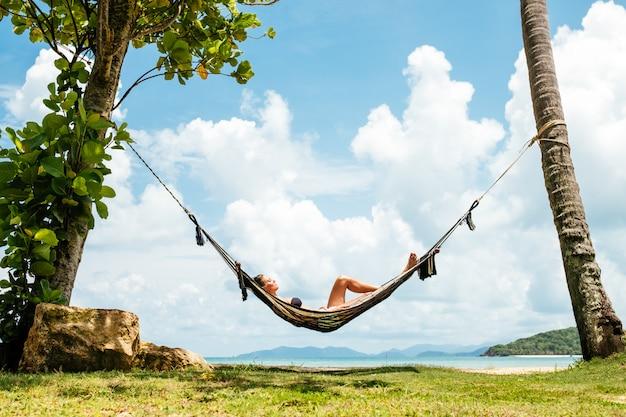 Szczęśliwa kobieta relaksuje w hamaku w czarnym bikini