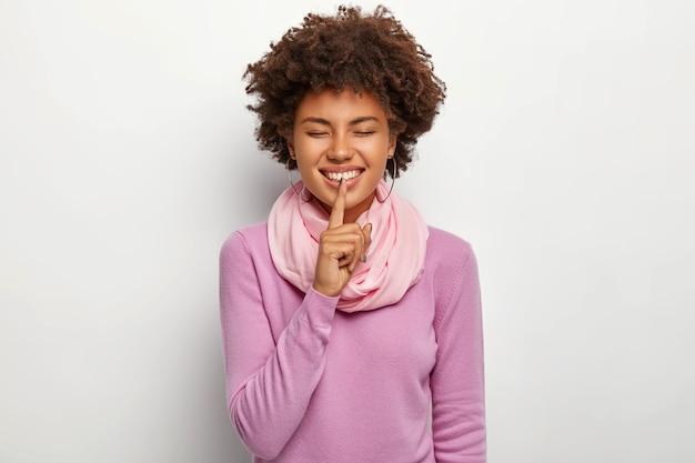 Szczęśliwa kobieta robi gest ciszy, trzyma palec wskazujący na ustach, cieszy się, że może podzielić się przyjemnym sekretem z najlepszą przyjaciółką, nosi fioletowy swobodny sweter