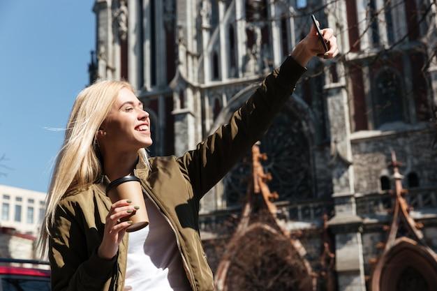 Szczęśliwa kobieta robi selfie na smartphone