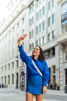 Szczęśliwa kobieta robi selfie na ulicy