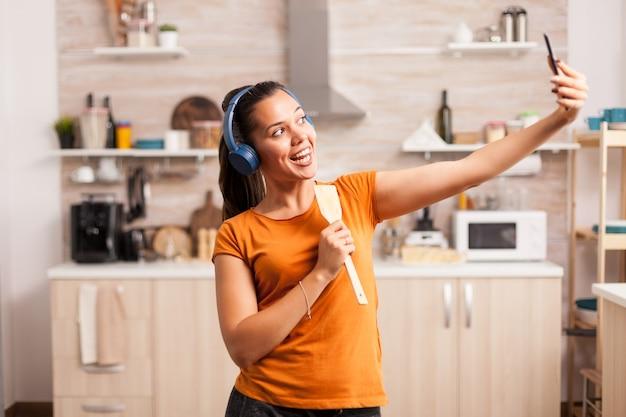 Szczęśliwa kobieta robi sobie rano selfie podczas śpiewania za pomocą łyżki