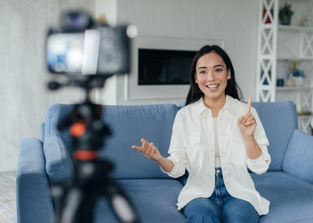 Szczęśliwa kobieta robi vlog w pomieszczeniu