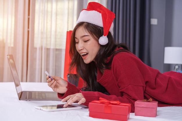 Szczęśliwa kobieta robi zakupy online dla bożenarodzeniowego prezenta z cyfrową pastylką i kredytową kartą na łóżku