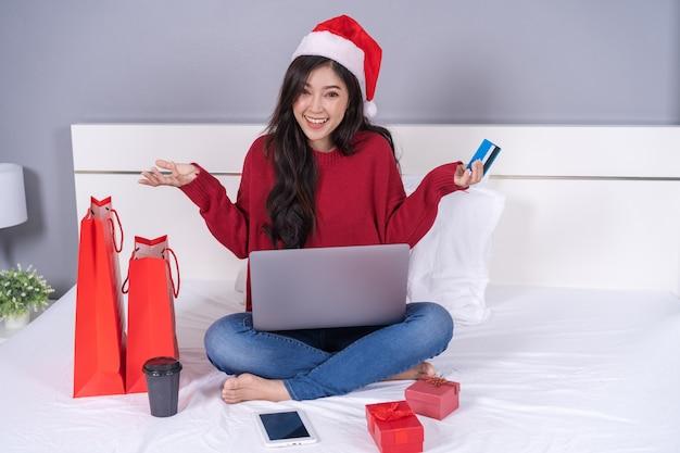 Szczęśliwa kobieta robi zakupy online dla bożenarodzeniowego prezenta z komputerowym laptopem i kredytową kartą na łóżku