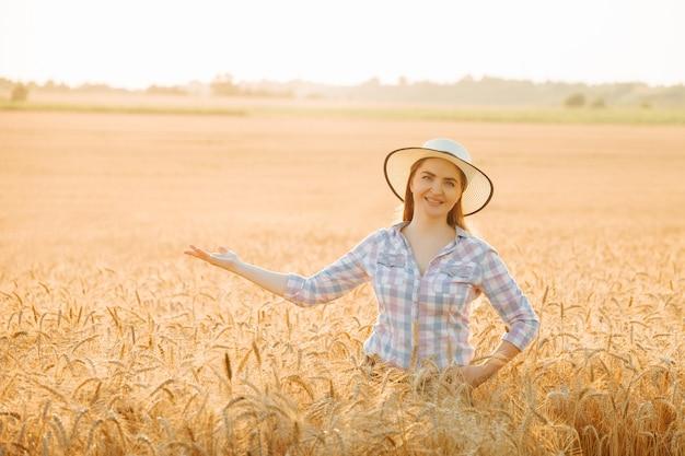 Szczęśliwa kobieta rolnik patrząca na kamerę w kapeluszu na polu pszenicy z wyciągniętą ręką rolnik amerykan...