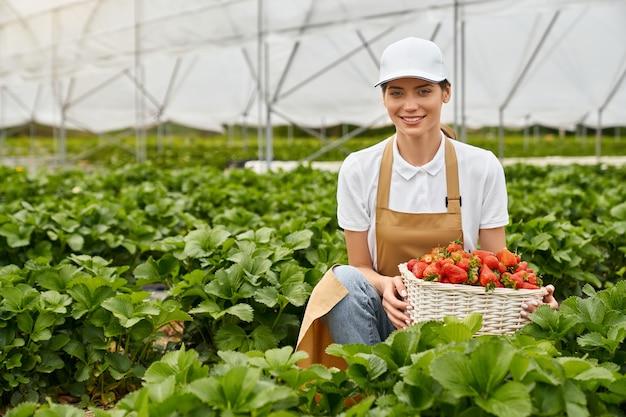 Szczęśliwa kobieta rolnik uśmiecha się i trzyma świeżą truskawkę