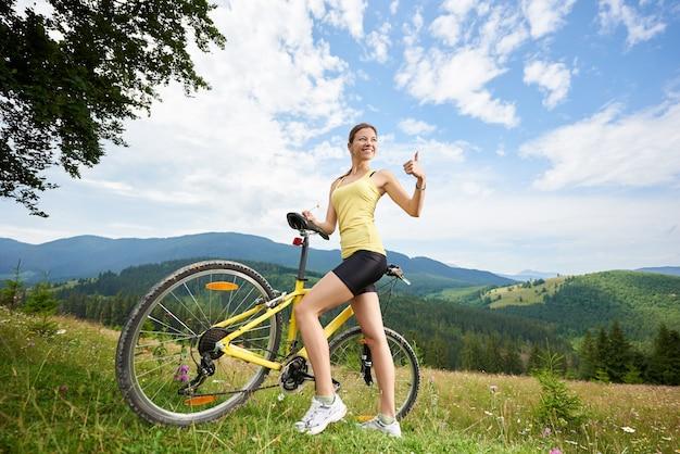 Szczęśliwa kobieta rowerzysta stojący na trawiastym wzgórzu, pokazując kciuk do góry, trzymając żółty rower górski, ciesząc się letni dzień w górach