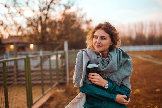 Szczęśliwa kobieta rozgrzewka z gorącą kawą w zimny jesienny poranek.