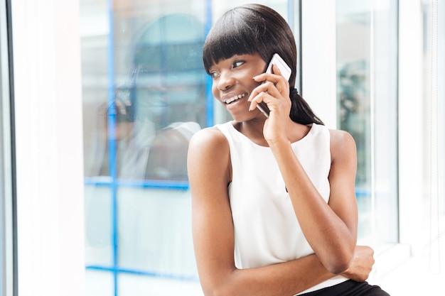 Szczęśliwa kobieta rozmawia przez telefon i patrzy w okno