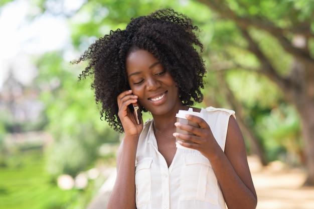 Szczęśliwa kobieta rozmawia przez telefon i picia kawy
