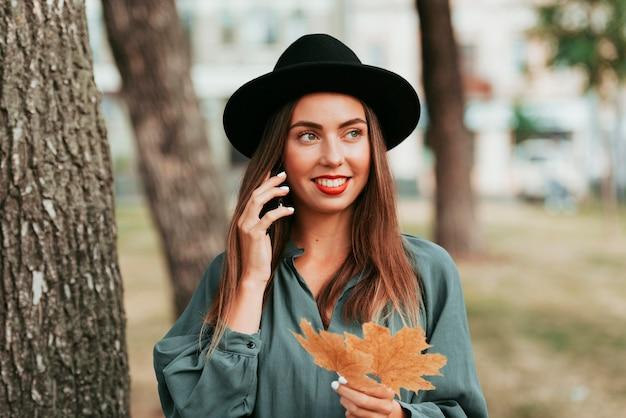 Szczęśliwa kobieta rozmawia przez telefon jesienią