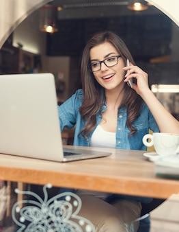 Szczęśliwa kobieta rozmawia przez telefon komórkowy i za pomocą laptopa w kawiarni