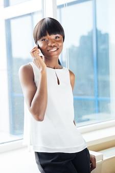 Szczęśliwa kobieta rozmawia przez telefon w biurze i patrzy na przód
