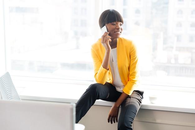 Szczęśliwa kobieta rozmawia przez telefon w biurze