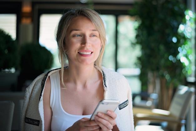 Szczęśliwa kobieta rozmawia przez telefon w restauracji