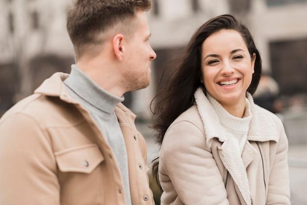 Szczęśliwa kobieta rozmawia z mężczyzną na zewnątrz