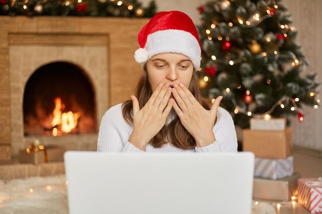 Szczęśliwa kobieta rozmawiająca z kimś przez wideorozmowę, witająca bliżej ludzi w święta bożego narodzenia, dmuchająca buziaki, siedząca w salonie przy choince i kominku.