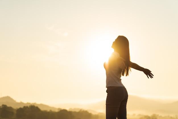 Szczęśliwa kobieta rozprzestrzeniania broni emocji wolności.