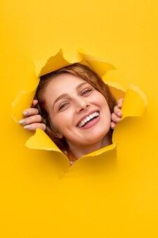 Szczęśliwa kobieta rozrywa papier i uśmiecha się
