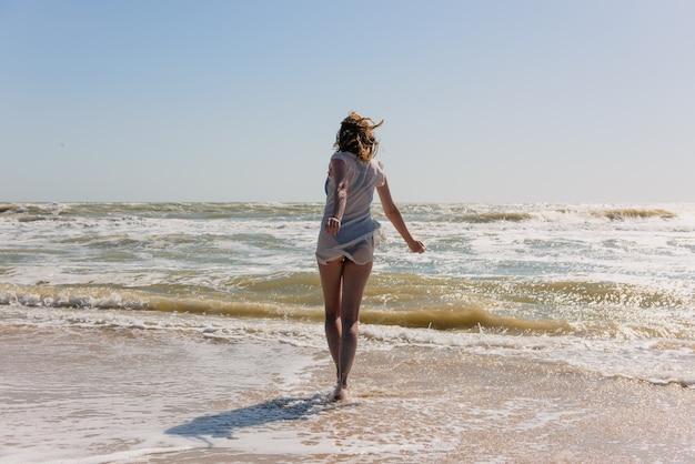 Szczęśliwa kobieta ruch i taniec nad morzem w ciągu dnia. kobieta z powrotem na plaży