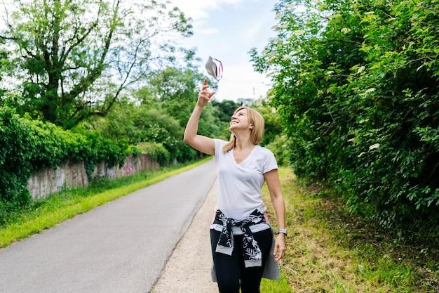 Szczęśliwa kobieta rzuca maskę w powietrze w zielonym otoczeniu
