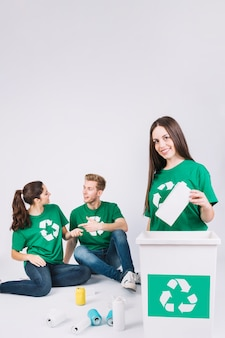 Szczęśliwa kobieta rzucając butelkę w kosz na śmieci z ikona recyklingu