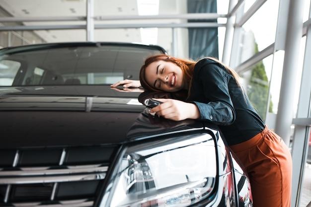 Szczęśliwa kobieta ściska jej nowy samochód