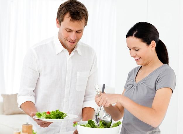 Szczęśliwa kobieta serwująca sałatkę swojemu chłopakowi na lunch