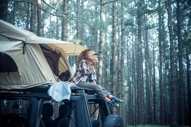 Szczęśliwa kobieta siada na dachu samochodu z zamontowanym na nim namiotem