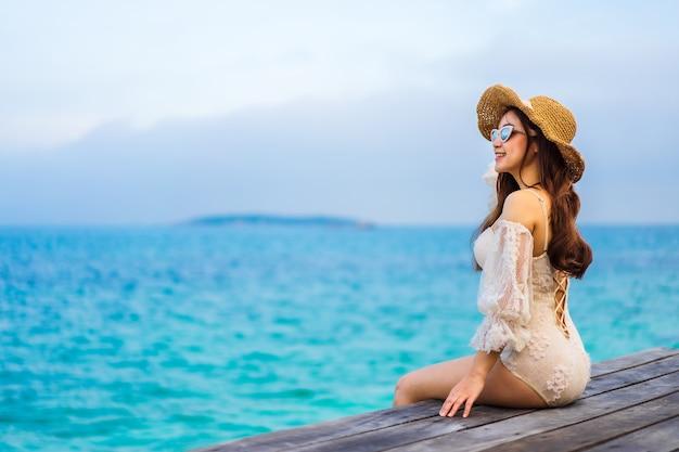 Szczęśliwa kobieta siedzi na drewnianym moście na plaży morskiej na wyspie koh munnork, rayong, tajlandia