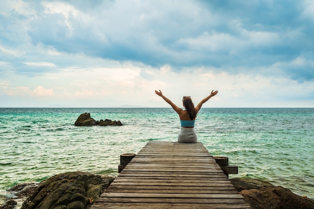 Szczęśliwa kobieta siedzi na drewnianym moście z podniesionym ramieniem na morzu na wyspie koh munnork, rayong, tajlandia
