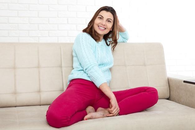Szczęśliwa kobieta siedzi na kanapie i relaksuje w domu.