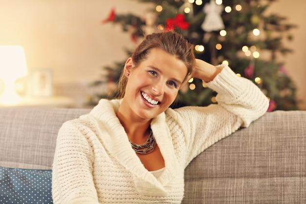 Szczęśliwa kobieta siedzi na kanapie nad dekoracjami świątecznymi
