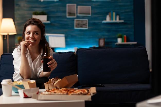 Szczęśliwa kobieta siedzi na kanapie oglądając film komediowy w telewizji wieczorem in