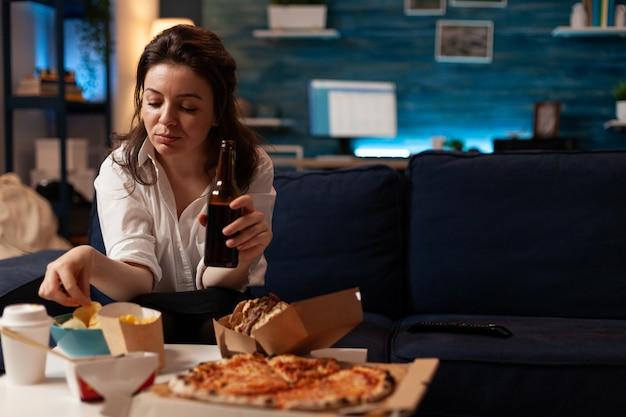 Szczęśliwa kobieta siedzi na kanapie oglądając film komediowy w telewizji wieczorem